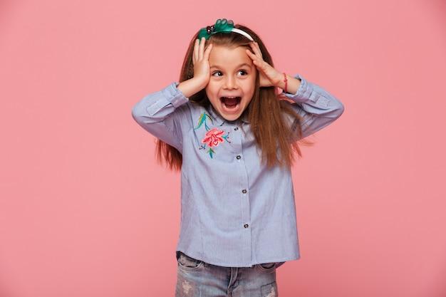Mooi meisje reageert emotioneel grijpend hoofd met beide handen blij en geschokt
