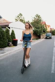 Mooi meisje rijden op een elektrische scooter in de zomer op straat