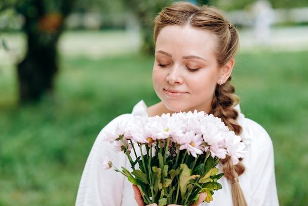 Mooi meisje ruikt witte bloemen buitenshuis