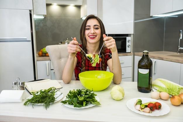 Mooi meisje salade van verse groenten eten tijdens het glimlachen en zitten in de keuken thuis.