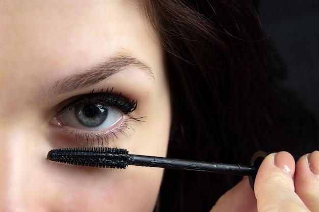 Mooi meisje schildert ogen met mascara close-up