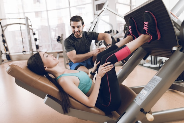 Mooi meisje schudt haar benen in de sportschool met een trainer.