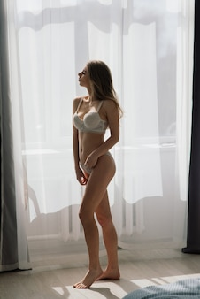 Mooi meisje sexy brunette in wit ondergoed poseren in een kamer in de interieur studio
