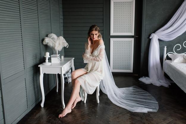 Mooi meisje sexy brunette in wit ondergoed poseren in een kamer in het interieur