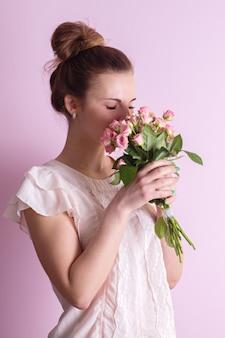 Mooi meisje snuiven een boeket roze rozen op valentijnsdag