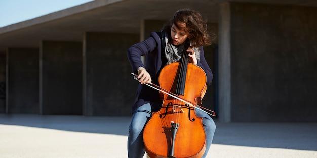 Mooi meisje speelt cello met passie in een concrete omgeving