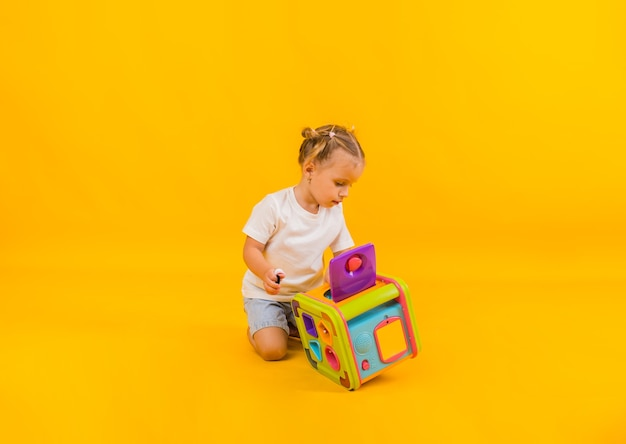 Mooi meisje speelt met een groot educatief speelgoed op een gele achtergrond met ruimte voor tekst