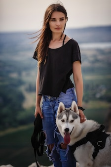 Mooi meisje speelt met een hond, grijze en witte husky, in de bergen bij zonsondergang. indisch meisje en haar wolf
