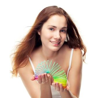 Mooi meisje speelt met een kleurrijke slinky