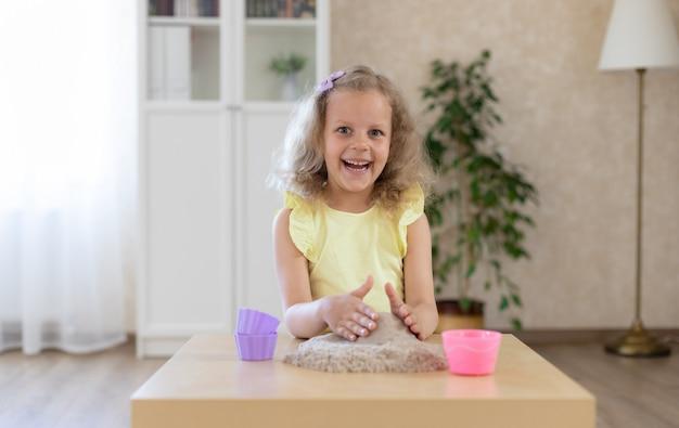 Mooi meisje spelen met kinetisch zand en een schop