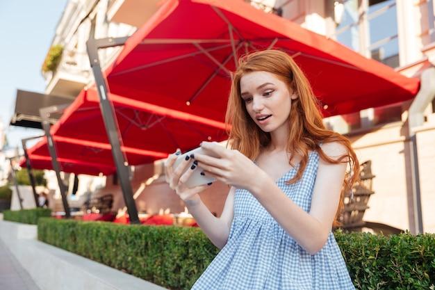 Mooi meisje spelen van games op mobiele telefoon