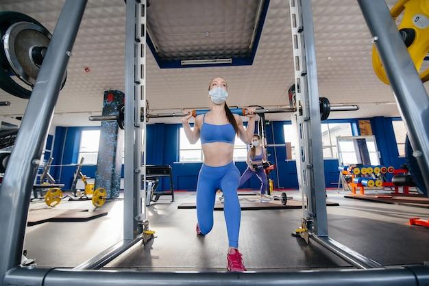 Mooi meisje sporten in de sportschool met een masker tijdens de pandemie