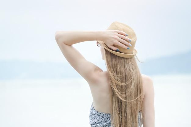 Mooi meisje staat bij de pier. zee en een kleine vuurtoren in de verte. achteraanzicht