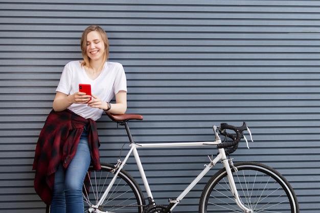 Mooi meisje staat met een fiets op de achtergrond van een muur