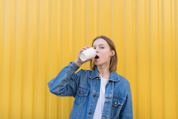 Mooi meisje staat op de achtergrond van de gele muur en drinkt koffie uit de beker.