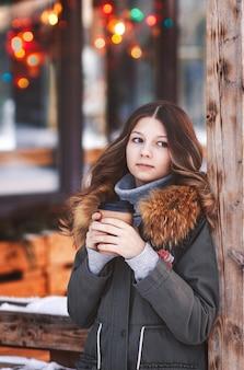 Mooi meisje staat op de open veranda van het café met een papieren kopje koffie in haar handen