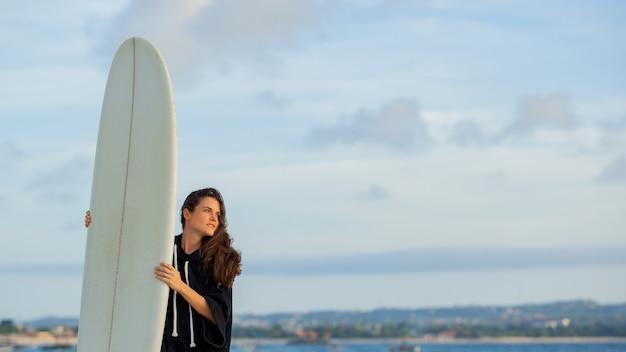 Mooi meisje staat op het strand met een surfplank.