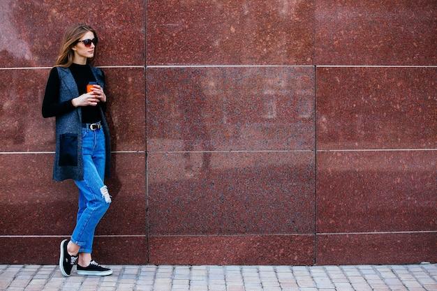 Mooi meisje staat tegen de muur met een kopje koffie op straat.