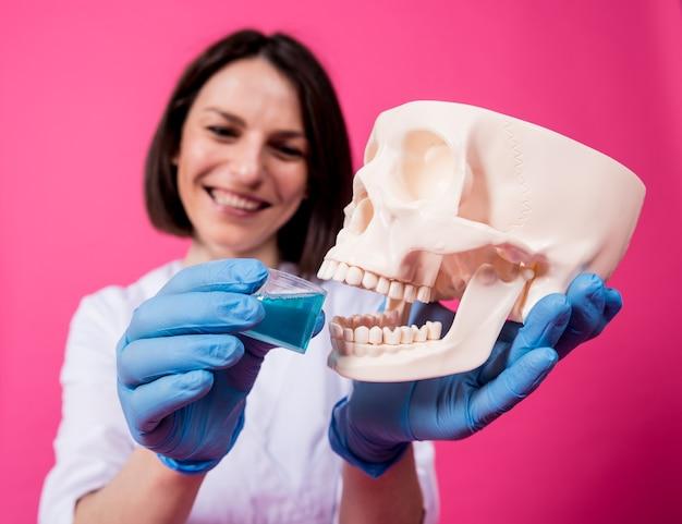 Mooi meisje stelt mondwater voor voor kunstmatige schedel