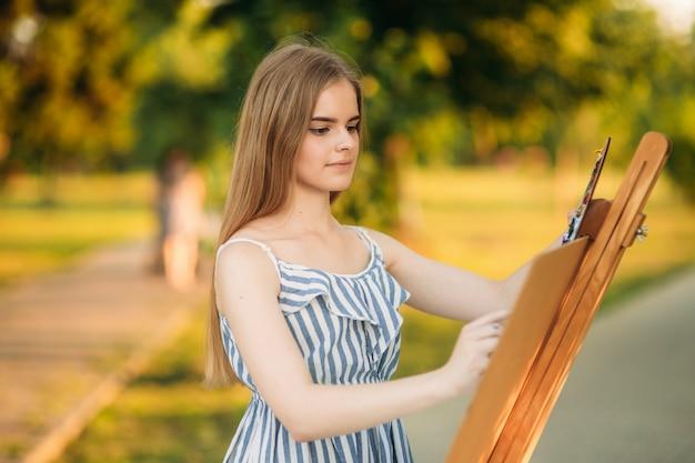 Mooi meisje tekent een foto in het park met behulp van een palet met verf en een spatel. schildersezel en canvas met een foto.