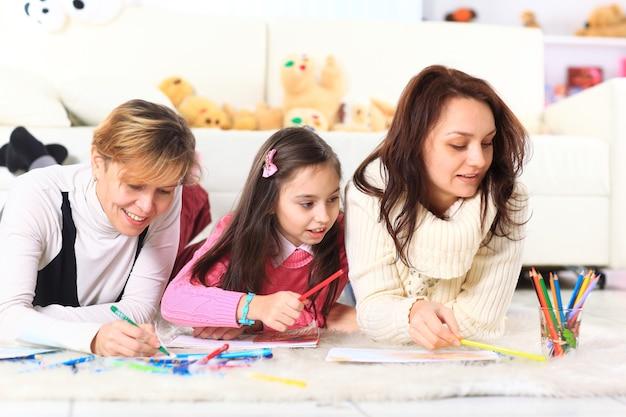 Mooi meisje tekent met zijn moeder en tante.