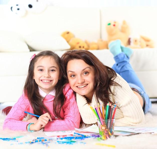 Mooi meisje tekent met zijn moeder