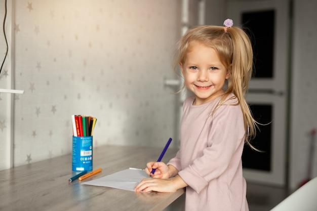 Mooi meisje tekent thuis met een potlood