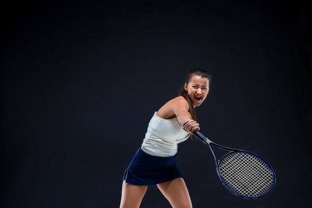 Mooi meisje tennisspeler met een racket op donkere achtergrond