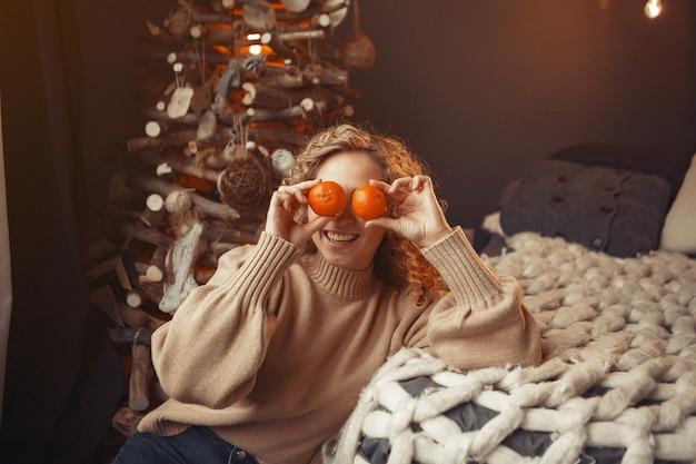 Mooi meisje thuis dichtbij kerstboom