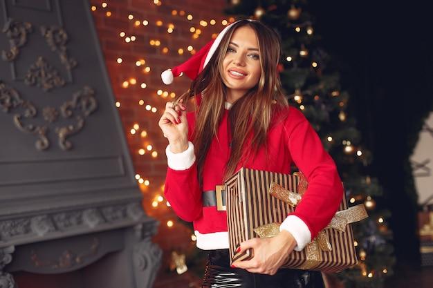 Mooi meisje thuis in het kostuum van een kerstman