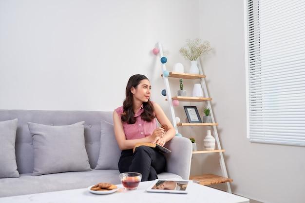 Mooi meisje thuis zittend op de bank, een boek lezend en een koffiepauze
