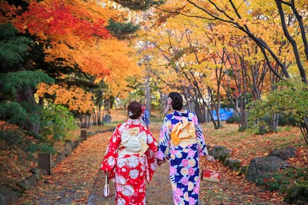 Mooi meisje twee die japanse traditionele kimono in de herfst draagt.