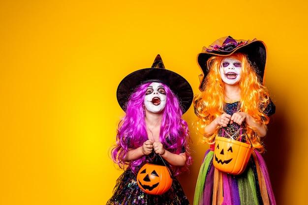 Mooi meisje twee in een heksenkostuum die en gezichten doen schrikken maken