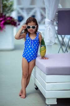Mooi meisje van 5 jaar met donker haar in een blauwe polka dot badpak en in zonnebril drinkt een cocktail op een zomervakantie bij het zwembad.