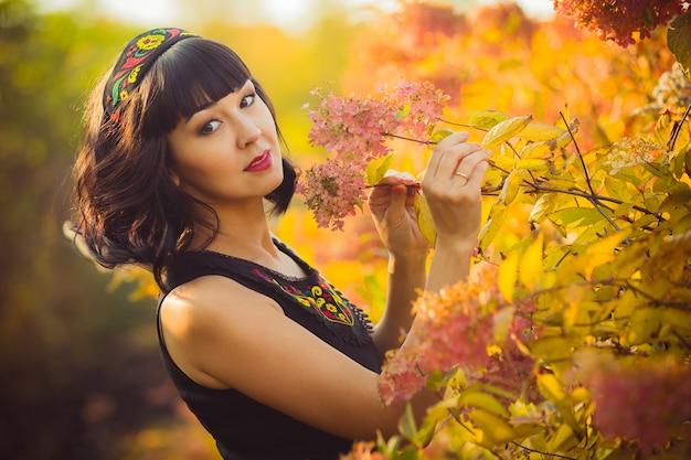 Mooi meisje van aziatische verschijning in de herfst in het park ruikende bloemen