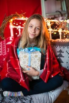 Mooi meisje van een jaar of tien, poseren voor een fotograaf in een kerstinterieur