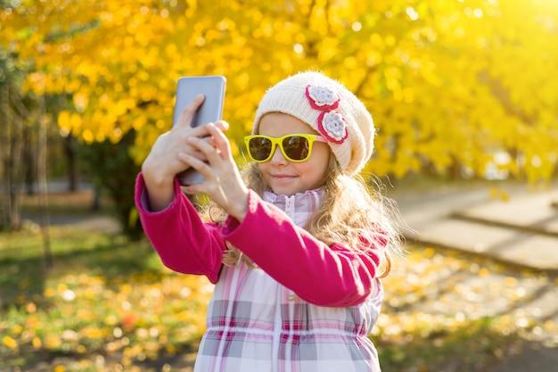 Mooi meisje van zeven jaar doen selfie met behulp van smartphone