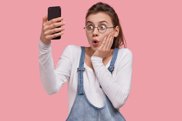 Mooi meisje verbaasd over ontvangen e-mail, maakt videogesprek om nieuws te delen met vriend op afstand, verbonden met snel internet houdt mobiel vast