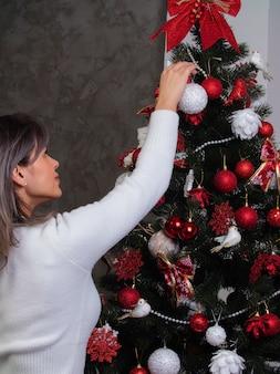 Mooi meisje verkleedt een kerstboom voor kerstmis
