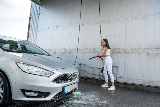 Mooi meisje wast het schuim met een waterpistool uit haar auto bij de zelfbedieningswasstraat