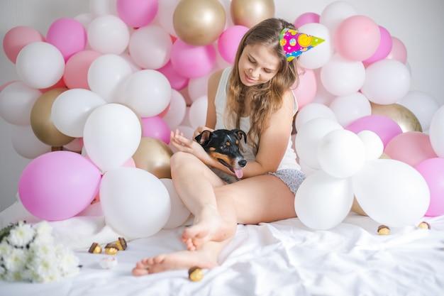 Mooi meisje werd wakker omringd door ballonnen op de dag van de verjaardag met haar hond