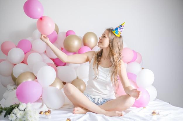 Mooi meisje werd wakker omringd door ballonnen op de dag van de verjaardag