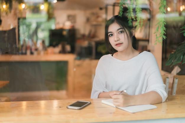 Mooi meisje werkt aan de tafel in het café