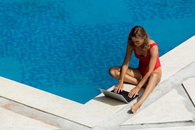 Mooi meisje werkt op de computer bij het zwembad