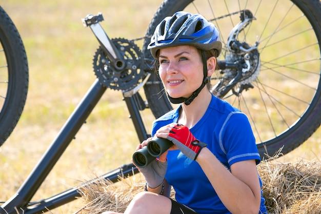 Mooi meisje wielrenner met een verrekijker in de hand op de fiets. sport en recreatie