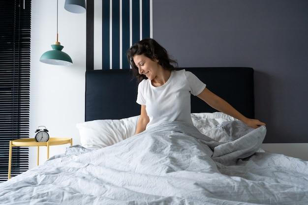 Mooi meisje wordt wakker in een goed humeur in een stijlvol appartement.