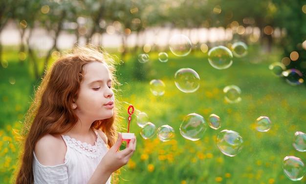 Mooi meisje zeepbellen blazen in park