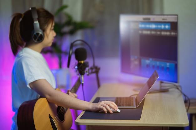 Mooi meisje zingt met hoofdtelefoon en speelt gitaar en neemt nieuw nummer op met microfoon in de thuisopnamestudio