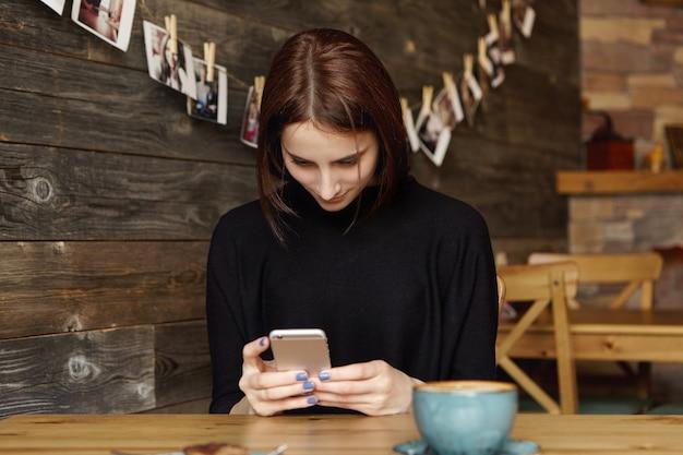 Mooi meisje zit aan café tafel met mok, met behulp van draadloze internetverbinding op mobiele telefoon
