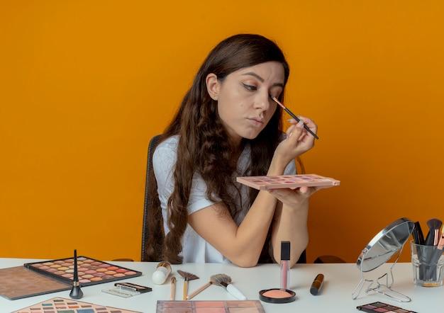 Mooi meisje zit aan de make-up tafel met make-up tools kijken naar spiegel houden schaduw palet en oogschaduw toe te passen met borstel geïsoleerd op een oranje achtergrond